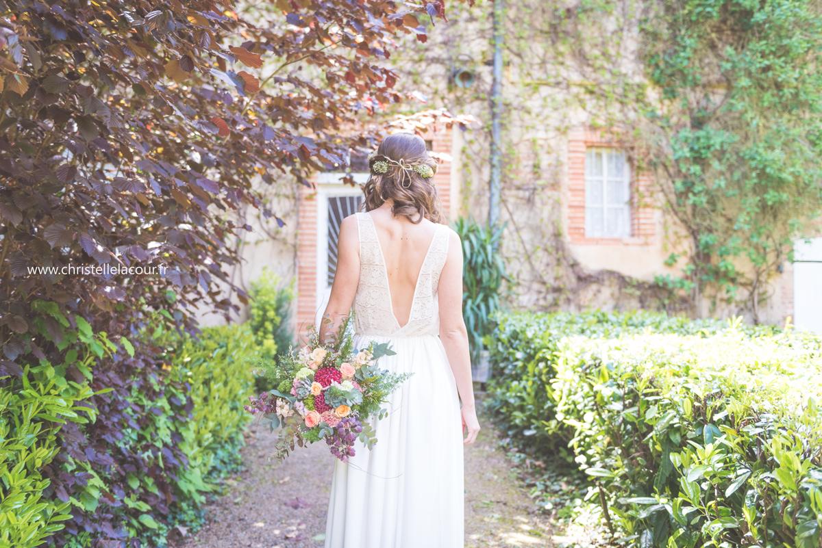 Le bouquet de la mariée et le dos nu de la robe de la mariée par Pauline Starck, mariage bohème