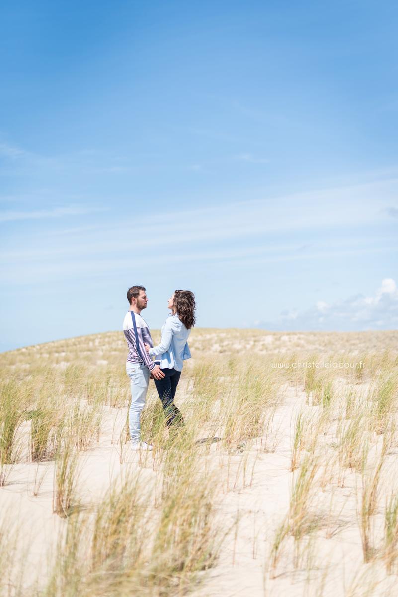 Deux amoureux seuls sur les dunes de l'Atlantique lors de leur séance love session