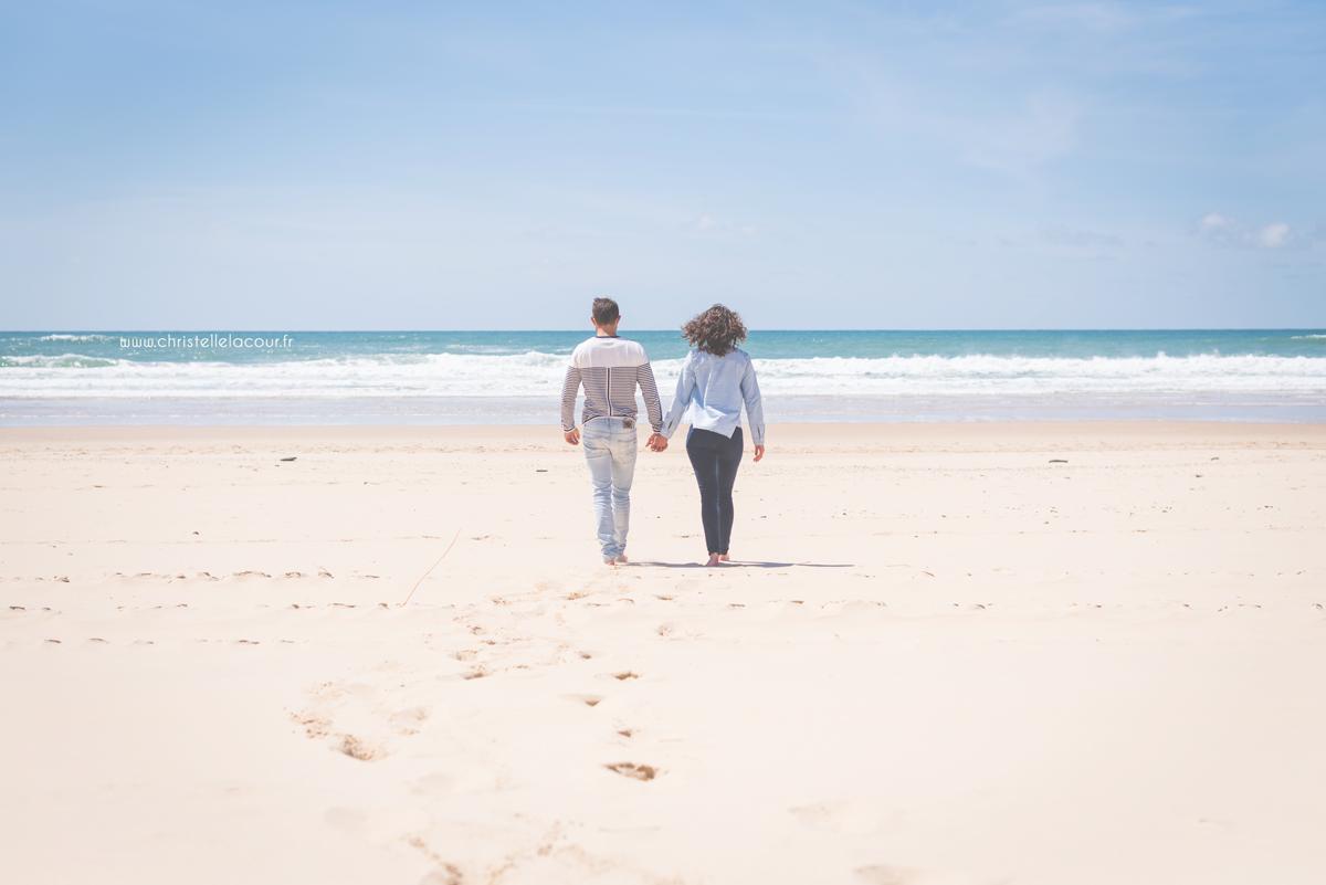 Couple d'amoureux s'avançant vers les vagues sur un plage de l'Atlantique