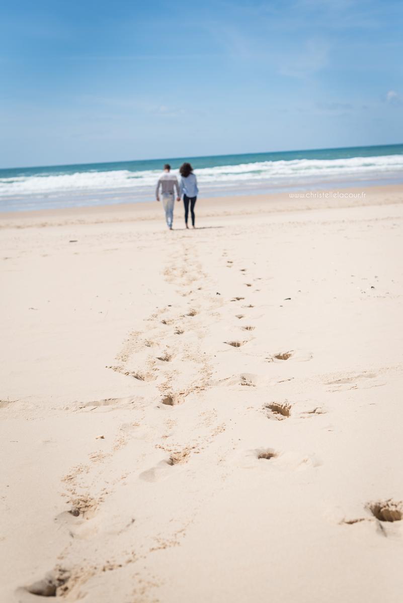 Empreintes de pas dans le sable de Lacanau d'un joli couple lors de leur love session avec Christelle Lacour Photographe