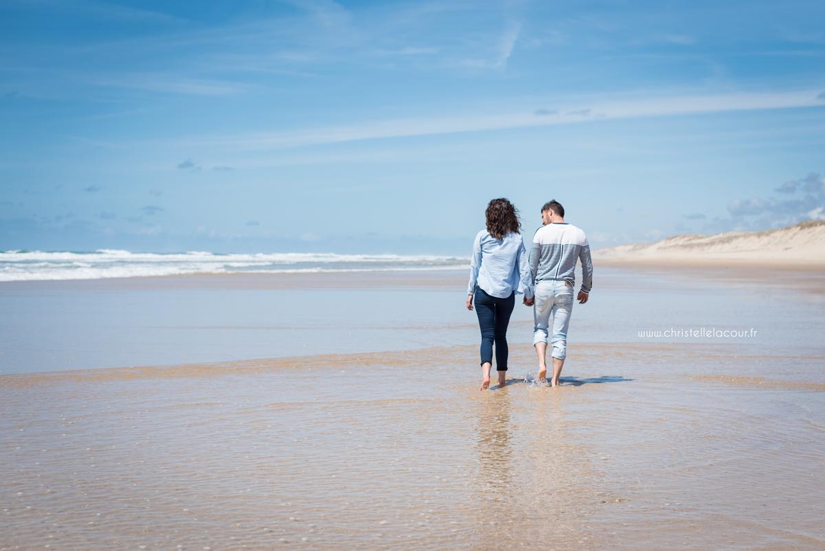 Amoureux marchant main dans la main et les pieds dans l'eau sur la plage de Lacanau