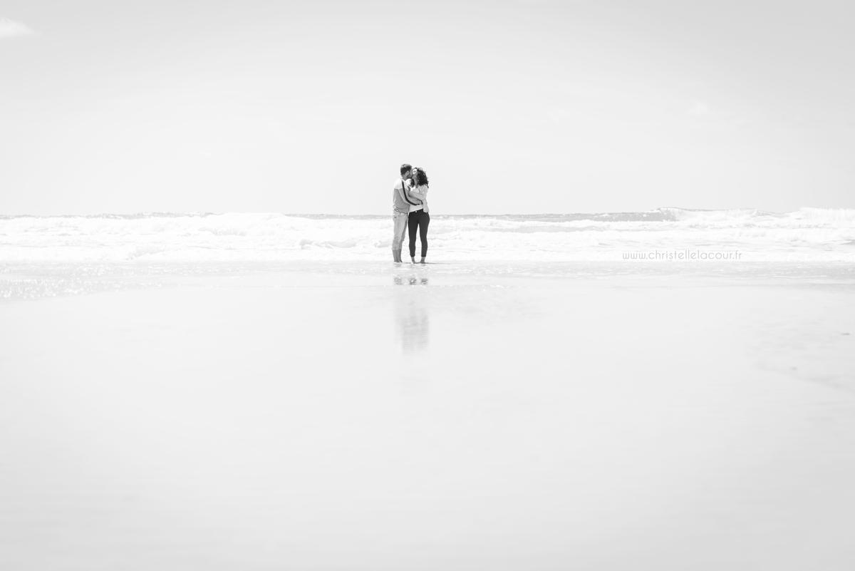 Amoureux s'embrassant les pieds dans l'eau sur la plage de Lacanau