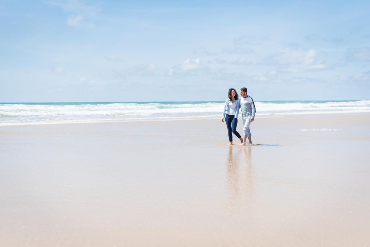 Photo couple sur la plage de Lacanau, amoureux marchant côte à côte les pieds dans l'eau