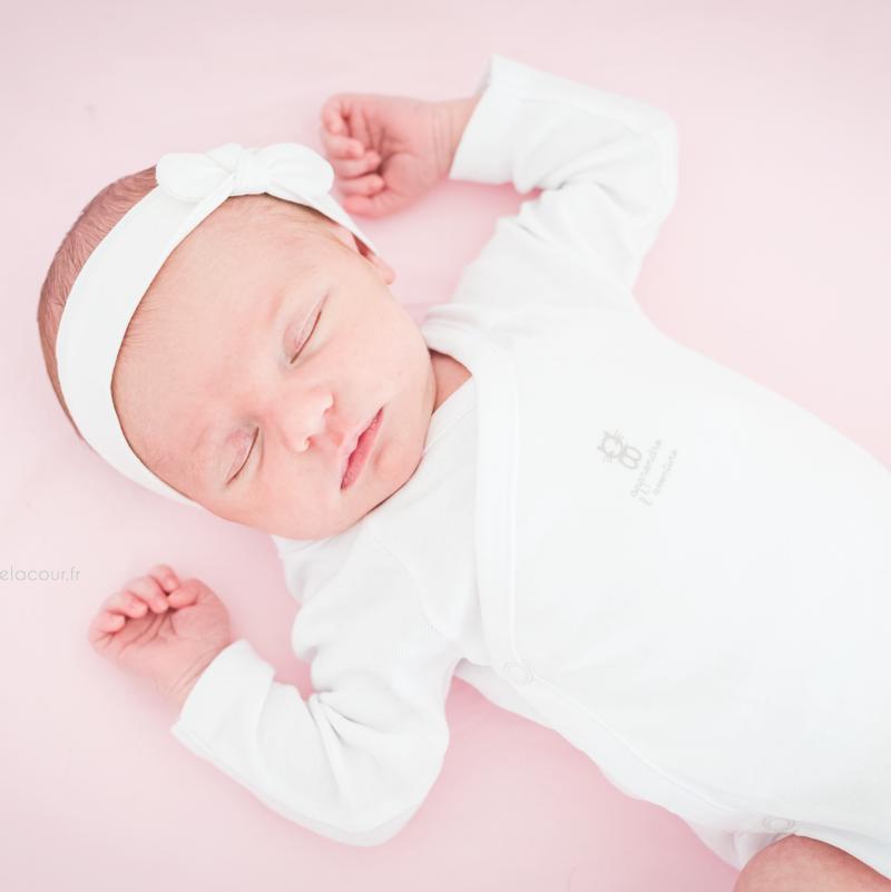 Photo nouveau-né à domicile, bébé adorable endormi dans son lit sur fond de rose et blanc