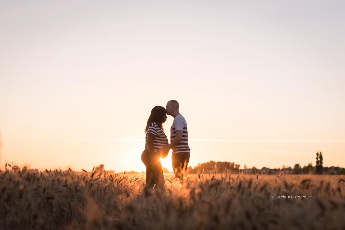 Photographe de grossesse à Toulouse, futurs parents et ventre rond à la lumière du coucher de soleil dans un champ de blé
