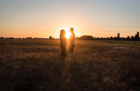 Photographe de grossesse à Toulouse, la silhouette des futurs parents et du ventre rond au coucher de soleil dans un champ de blé