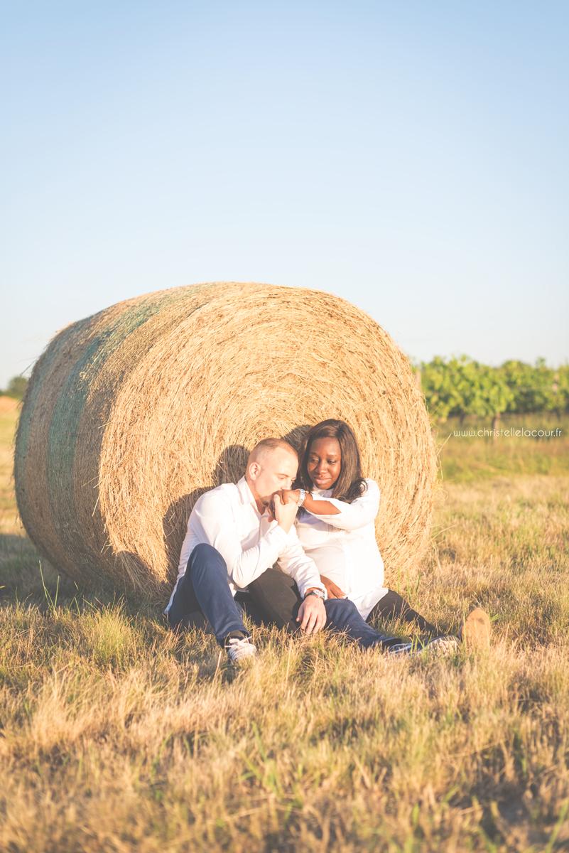 Séance grossesse à Toulouse, couple de futurs parents adossés à une botte de paille au coucher de soleil