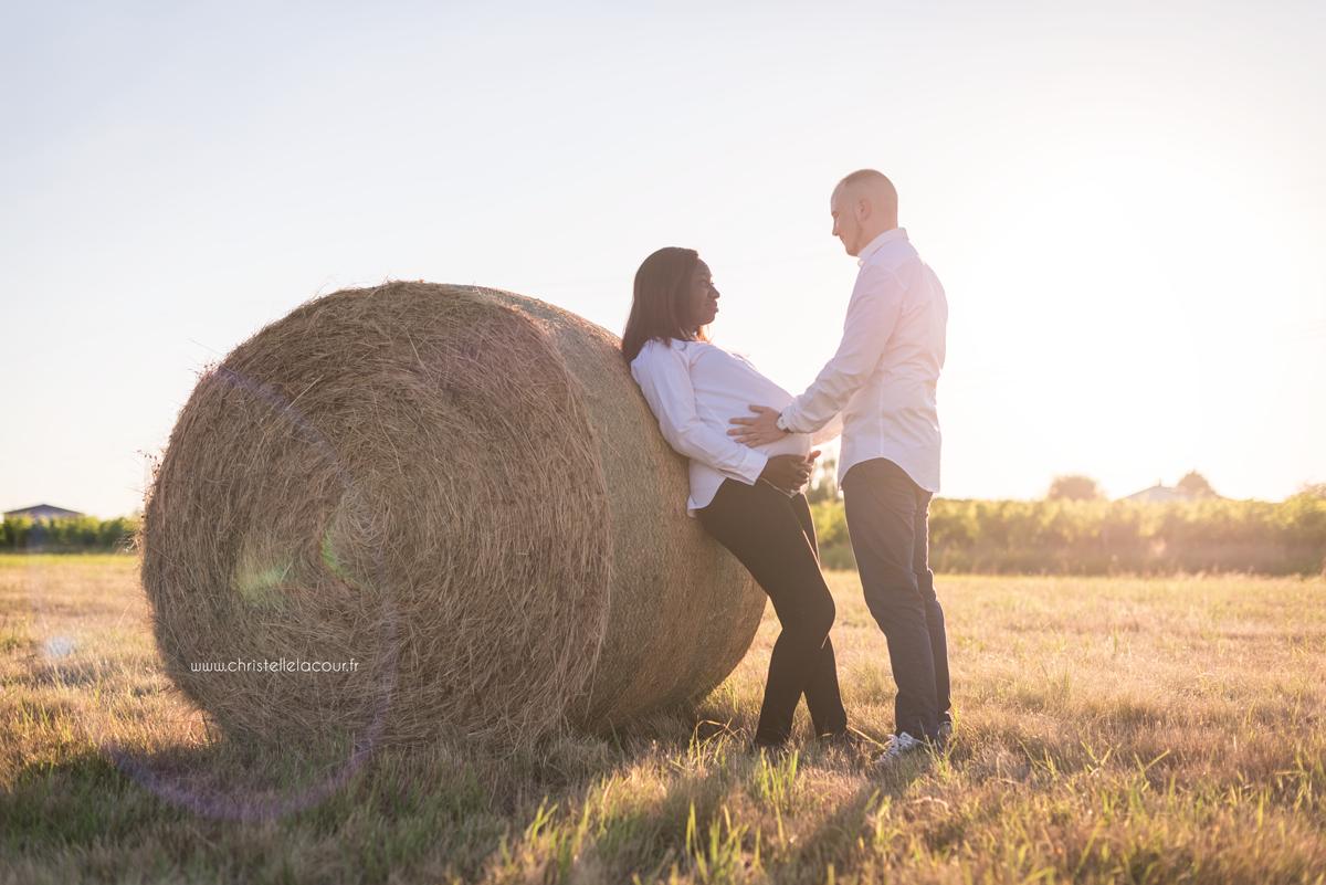 Photographe de grossesse à Toulouse, couple de futurs parents adossés à une botte de paille au coucher de soleil