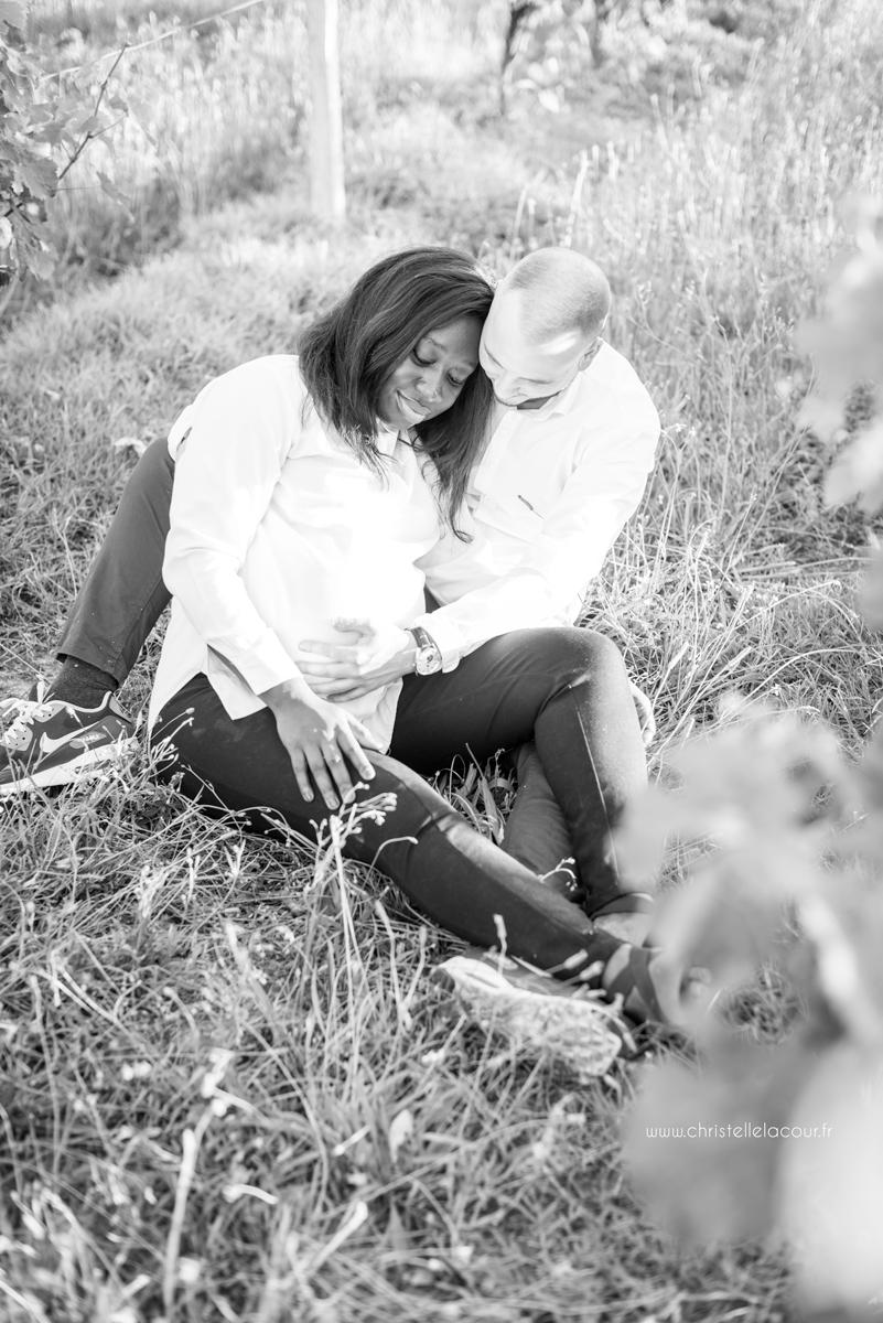Séance grossesse à Toulouse, pause tendre pour ces futurs parents assis dans les vignes en noir et blanc