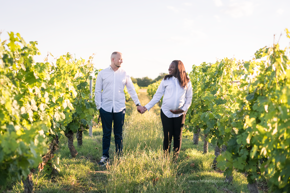 Photographe de grossesse à Toulouse, les futurs parents main dans la main dans les vignes de Fronton au coucher de soleil