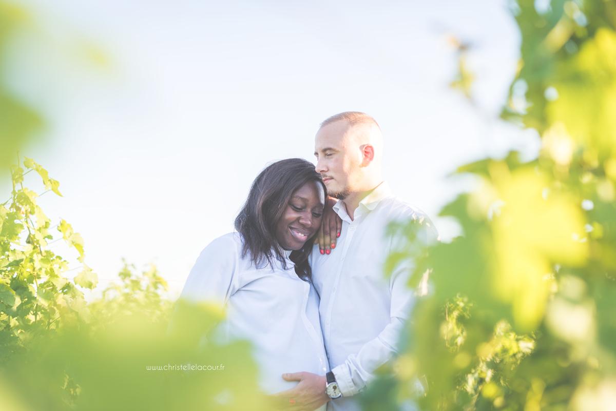 Photographe de grossesse à Toulouse, gestes tendres des futurs parents cachés entre les vignes au coucher de soleil un soir d'été
