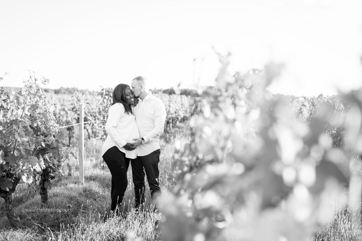 Photographe de grossesse à Toulouse, le bisou des futurs parents dans les vignes en noir et blanc