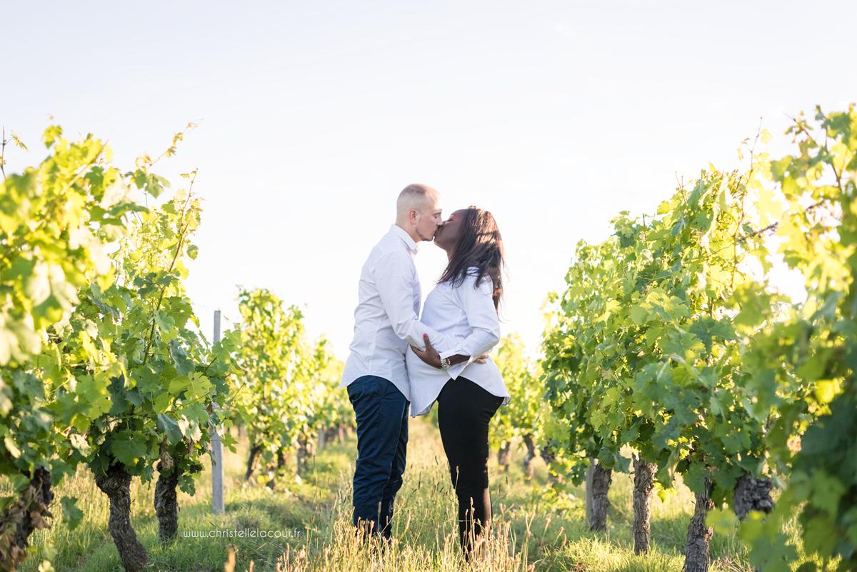 Photographe de grossesse à Toulouse, le bisou des futurs parents dans les vignes au coucher de soleil