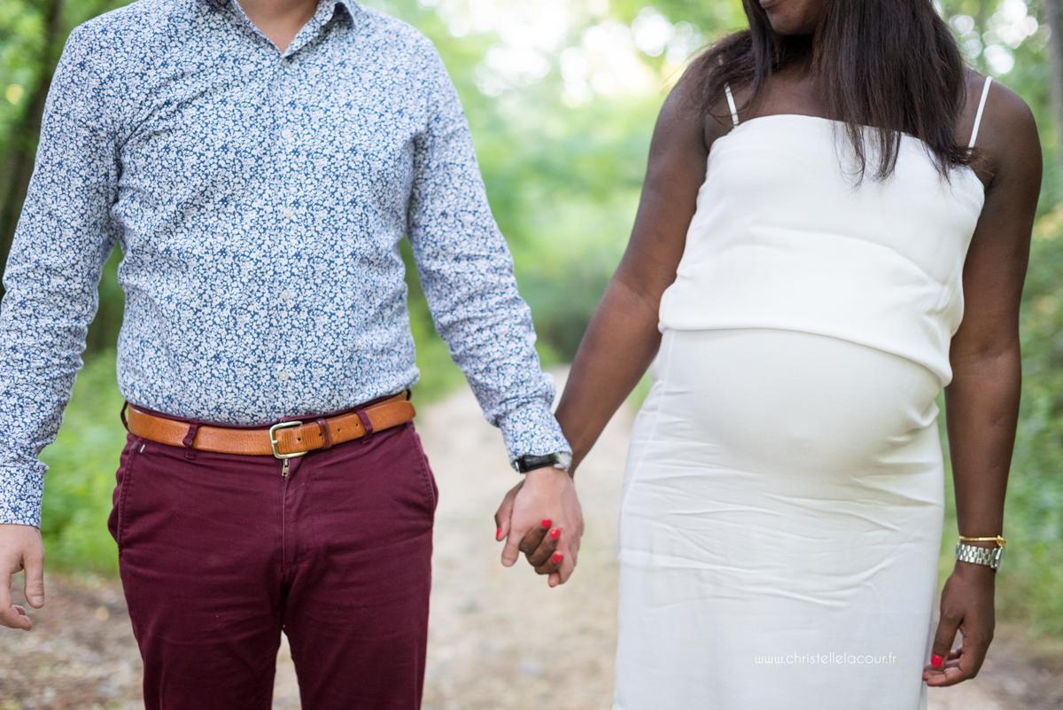 Séance photo de grossesse en couple dans la forêt, les futurs parents mains dans la main