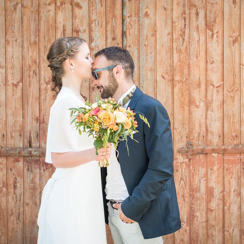 Photos de couple devant la porte de la grange, mariage fun et coloré aux Arches de la Jinolié dans le Tarn