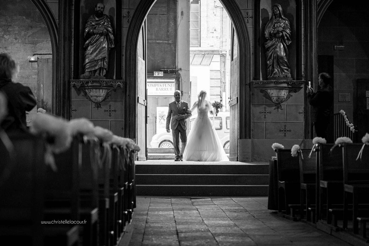 Photographe de mariage à Toulouse au Domaine Beausoleil, l'entrée de la mariée dans l'église au bras de son papa en noir et blanc
