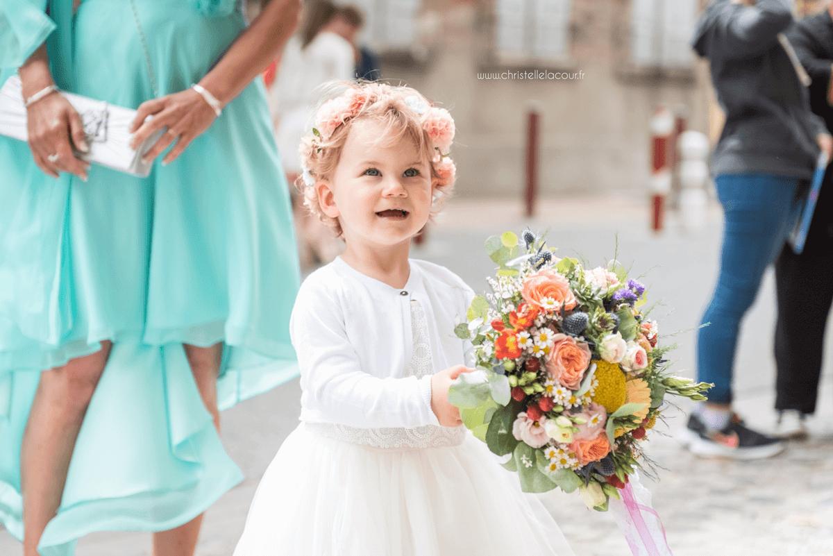 Photographe de mariage à Toulouse au Domaine Beausoleil, la fille des mariés, fière de tenir le bouquet de sa maman