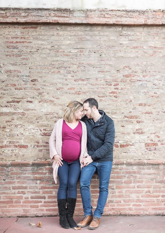 Photo de couple de parents à Toulouse devant un mur de briques rose