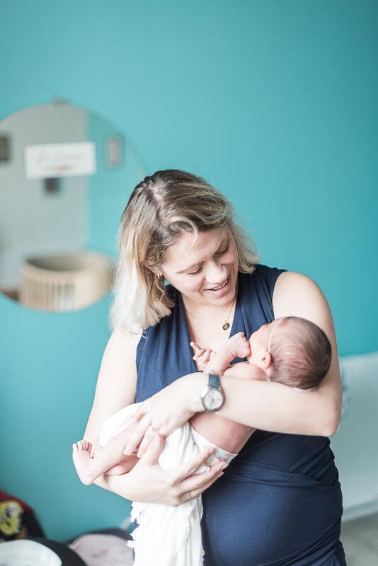 Photo de bébé dans les bras de maman pendant une séance photo de naissance à Toulouse