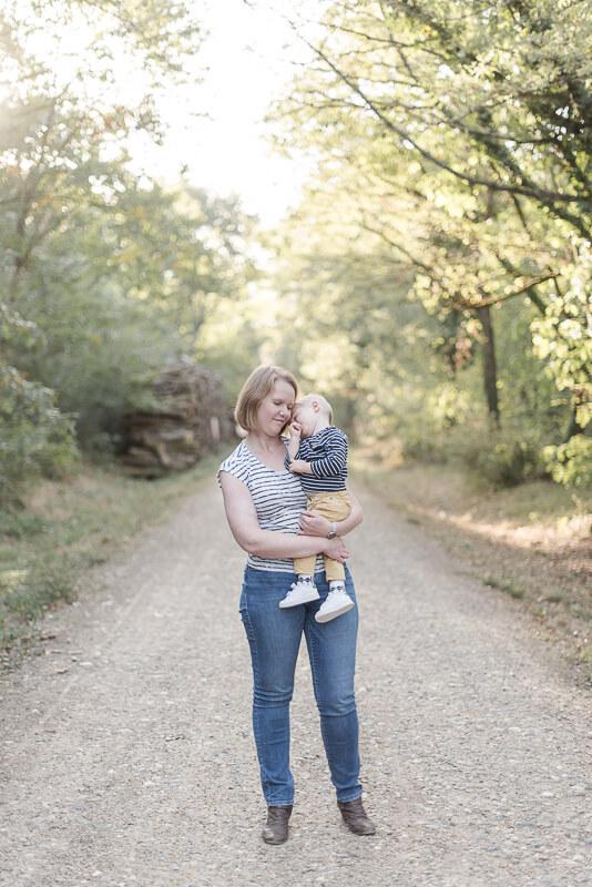 Photo de bébé de deux ans dans les bras de sa mère lors d'une séance photo de famille en forêt à Toulouse