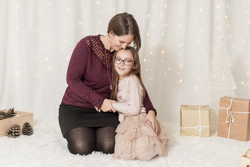 Séance photo mère et fille dans un décor studio de Noël