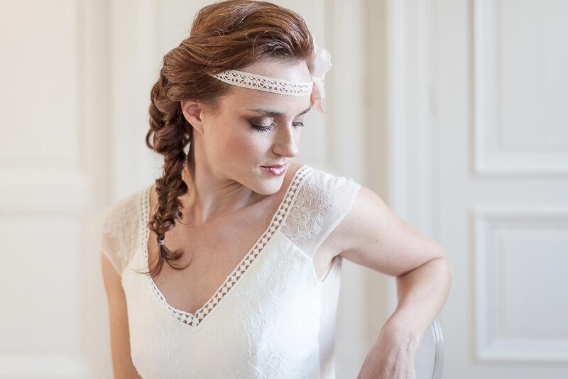 Headband pour mariée bohème avec une grosse fleur en tissu corail portée sur la tempe
