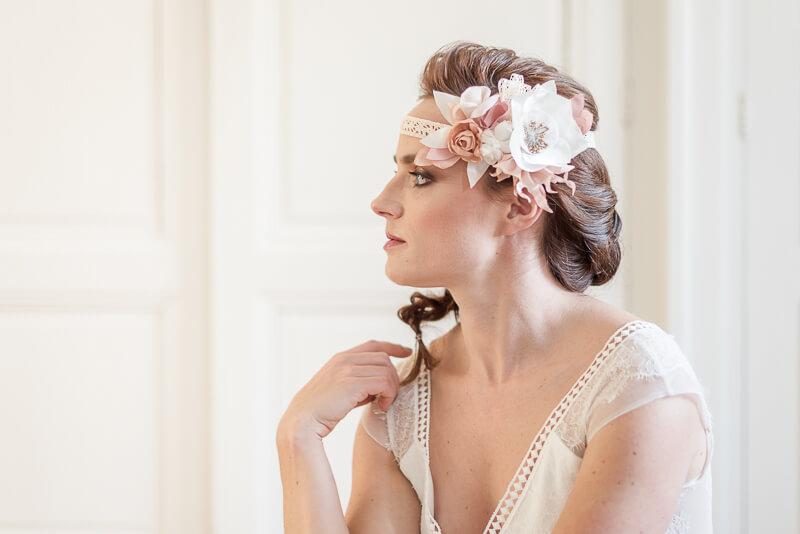 Headband pour mariée bohème avec de grosses fleurs en tissu corail et blanc portées sur la tempe