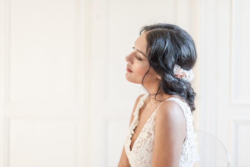 Demi-couronne de fleurs en tissu corail et blanc portée sur l'arrière de la tête pour coiffure de mariée