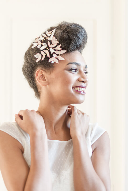Bijou de tête en laiton orné de petites feuilles de tissu pêche et blanc à porter sur le côté d'un chignon de mariée