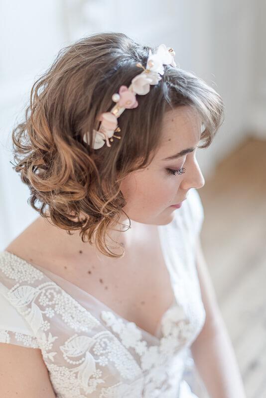 Couronne serre-tête de fleurs en tissu comme bijou de tête de mariée sur cheveux bouclés et courts