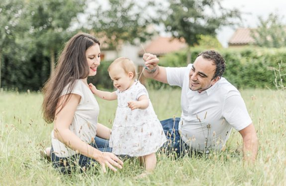 Séance photo de famille en extérieur près de Toulouse en été pour les premiers pas d'une petite fille