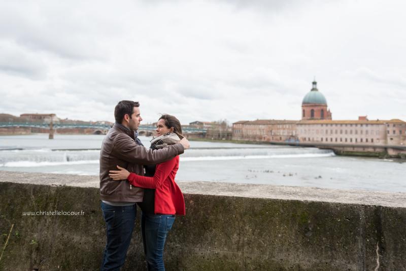 Séance photo de grossesse au centre ville de Toulouse, deux futurs parents amoureux sur les berges de la Garonne près du Bazacle