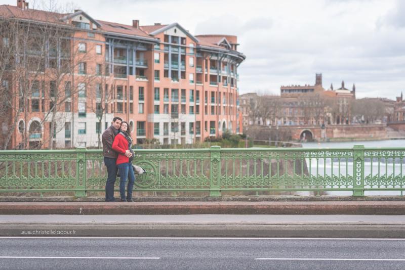 Séance photo de grossesse au centre ville de Toulouse, deux futurs parents amoureux sur le pont des Catalans