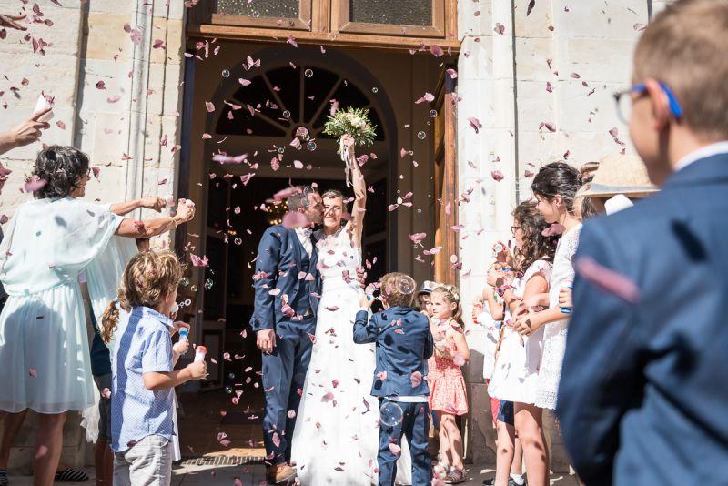 Sortie des mariés de l'église de Briatexte avec lancer de pétales de rose, mariage dans le Tarn, Christelle Lacour Photographe